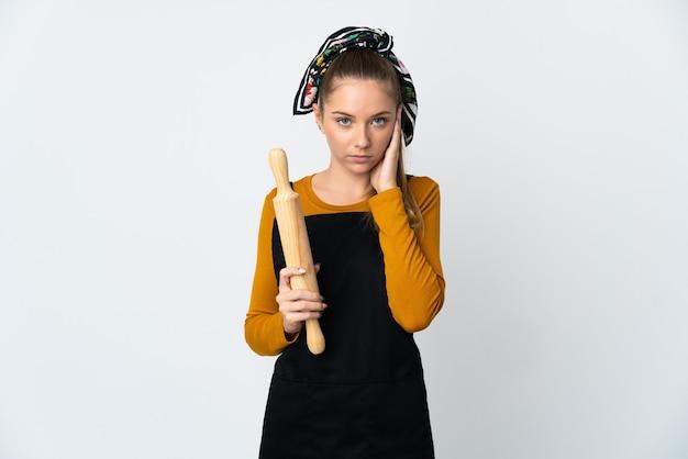 Jeune femme lituanienne tenant un rouleau à pâtisserie isolé sur fond blanc frustré et couvrant les oreilles