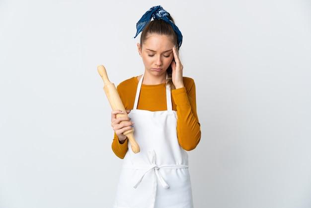 Jeune femme lituanienne tenant un rouleau à pâtisserie isolé sur fond blanc avec des maux de tête