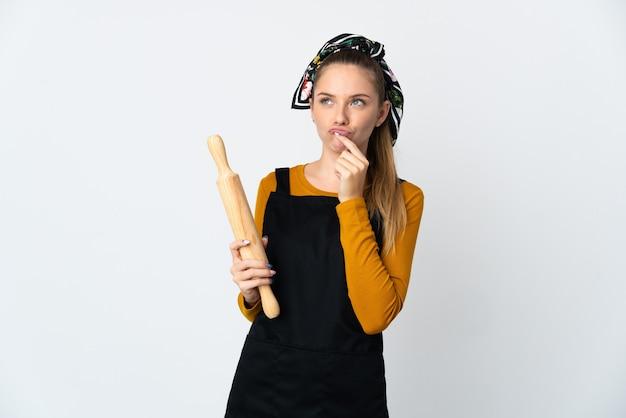 Jeune femme lituanienne tenant un rouleau à pâtisserie isolé sur un mur blanc ayant des doutes tout en regardant