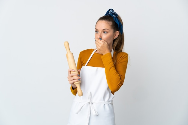 Jeune femme lituanienne tenant un rouleau à pâtisserie isolé sur un mur blanc faisant un geste de surprise tout en regardant sur le côté