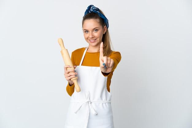 Jeune femme lituanienne tenant un rouleau à pâtisserie isolé sur un mur blanc montrant et en soulevant un doigt