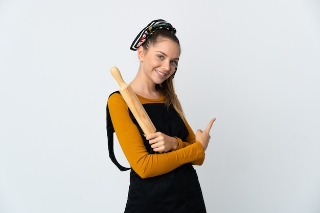 Jeune femme lituanienne tenant un rouleau à pâtisserie isolé sur un mur blanc pointant vers l'arrière
