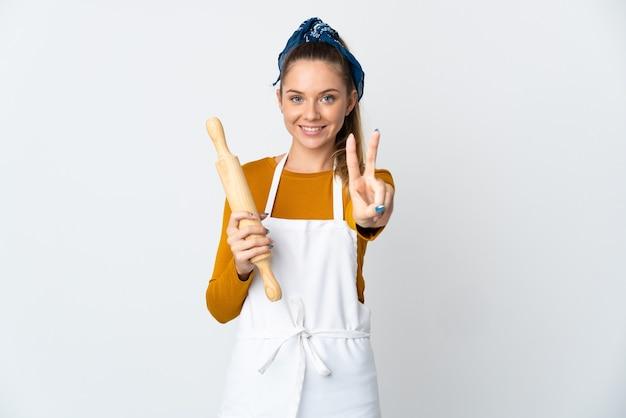 Jeune femme lituanienne tenant un rouleau à pâtisserie isolé sur mur blanc souriant et montrant le signe de la victoire