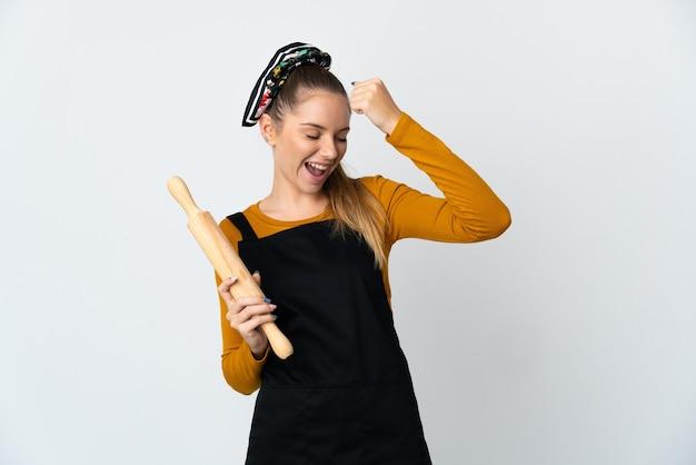 Jeune femme lituanienne tenant un rouleau à pâtisserie isolé