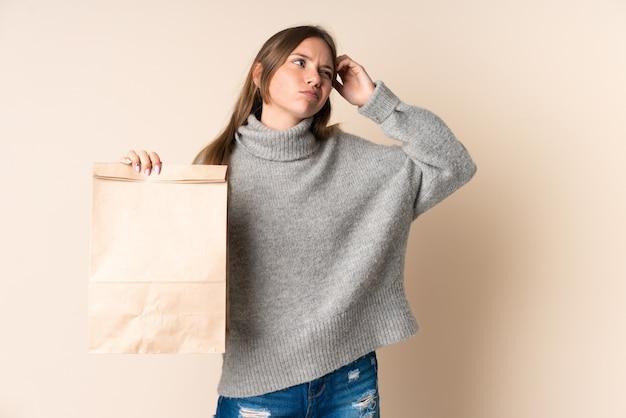 Jeune femme lituanienne tenant un sac d'épicerie ayant des doutes et avec l'expression du visage confus