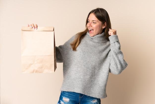 Jeune femme lituanienne tenant un sac d'épicerie célébrant une victoire