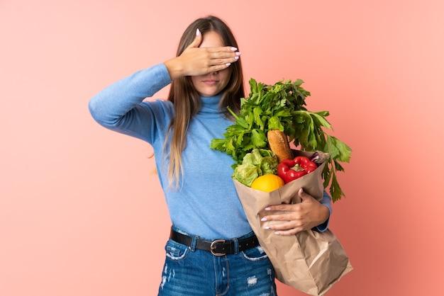 Jeune femme lituanienne tenant un sac d'épicerie couvrant les yeux par les mains. je ne veux pas voir quelque chose