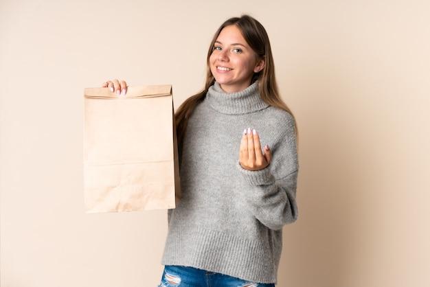 Jeune femme lituanienne tenant un sac d'épicerie invitant à venir avec la main. heureux que tu sois venu