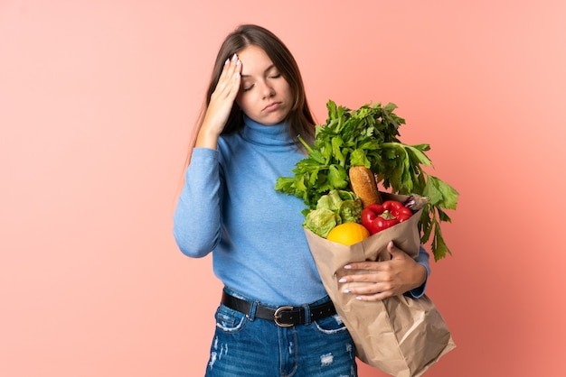 Jeune femme lituanienne tenant un sac d'épicerie avec maux de tête