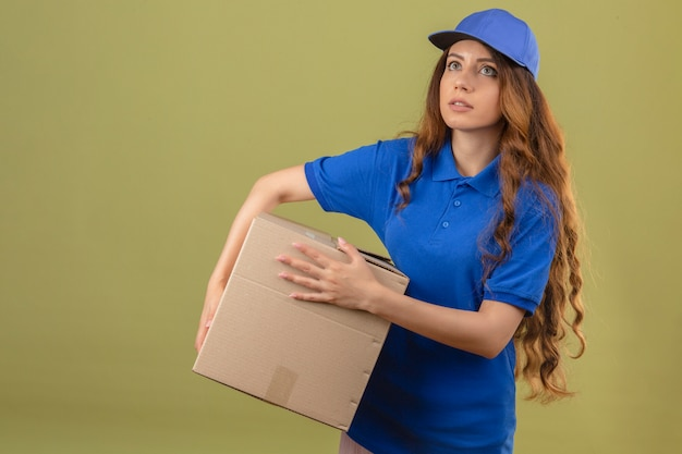 Jeune femme de livraison aux cheveux bouclés portant un polo bleu et une casquette debout avec boîte en carton à la fatigue sur fond vert isolé