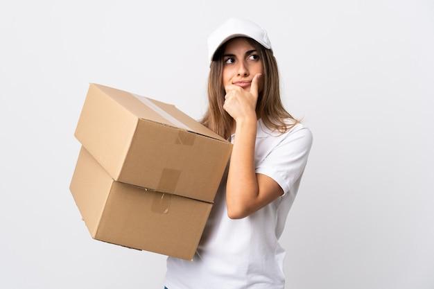 Jeune femme de livraison sur blanc isolé ayant des doutes et avec l'expression du visage confus