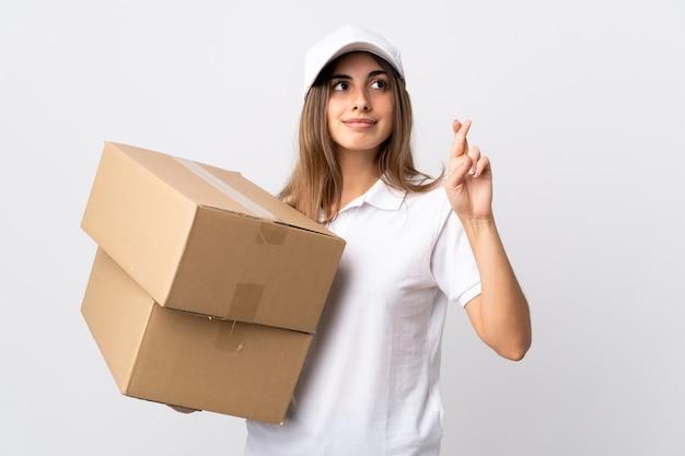 Jeune femme de livraison sur blanc isolé avec les doigts qui se croisent et souhaitant le meilleur