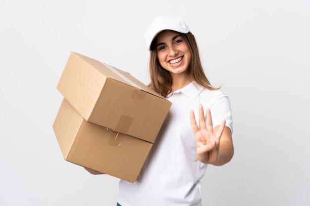 Jeune femme de livraison sur blanc isolé heureux et en comptant quatre avec les doigts