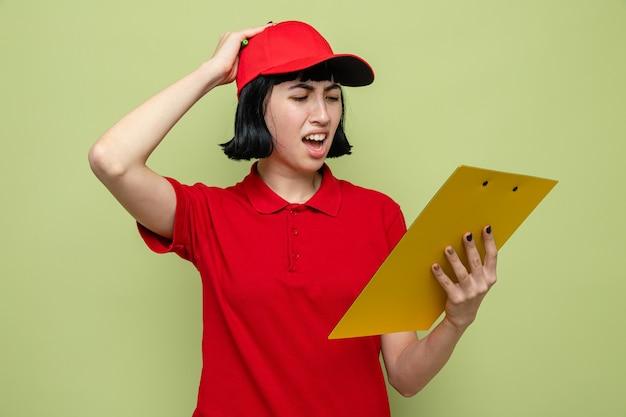 Jeune femme de livraison caucasienne déçue tenant et regardant le presse-papiers