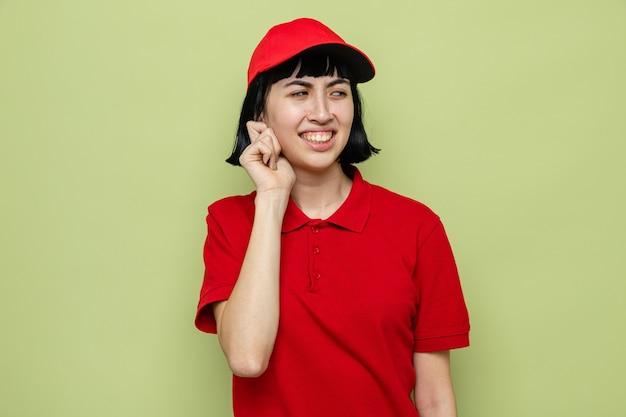 Jeune femme de livraison caucasienne mécontente tenant son oreille et regardant de côté