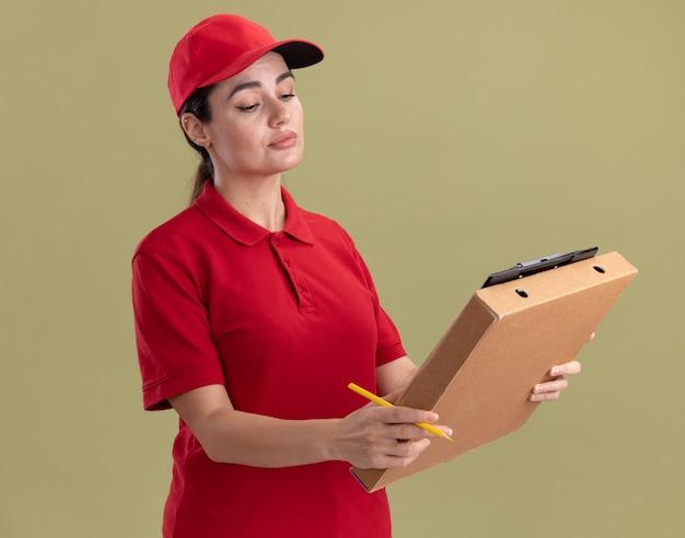 Jeune femme de livraison concentrée en uniforme et casquette tenant le presse-papiers du paquet de pizza et un crayon regardant le presse-papiers