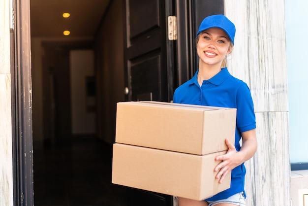 Jeune femme de livraison à l'extérieur tenant des boîtes avec une expression heureuse