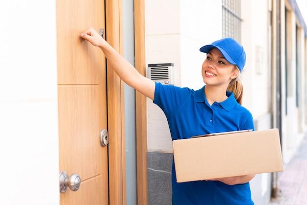 Jeune femme de livraison à l'extérieur tenant des boîtes et frappant à la porte