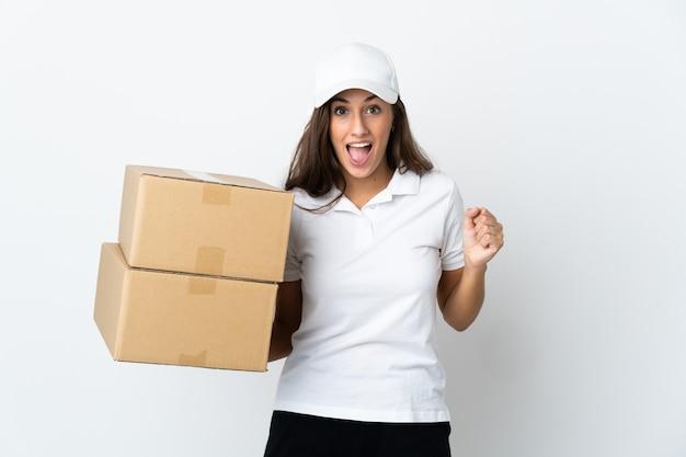 Jeune femme de livraison sur fond blanc isolé célébrant une victoire en position de vainqueur