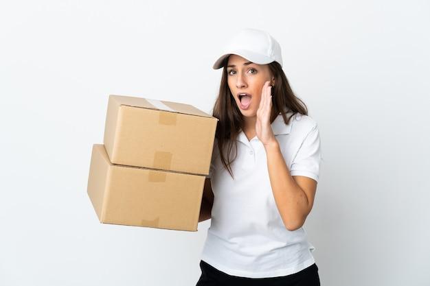 Jeune femme de livraison sur fond blanc isolé chuchotant quelque chose avec un geste de surprise tout en regardant sur le côté
