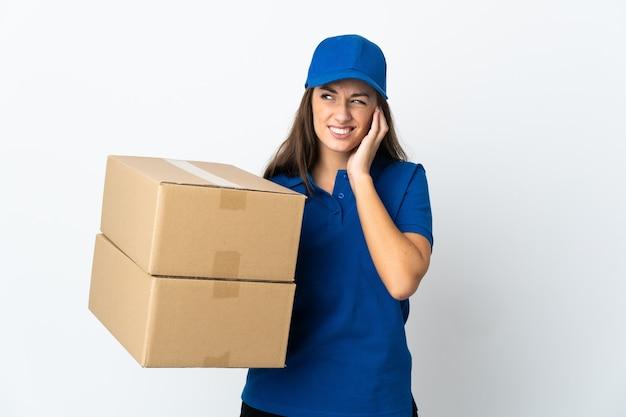 Jeune femme de livraison sur fond blanc isolé frustré et couvrant les oreilles