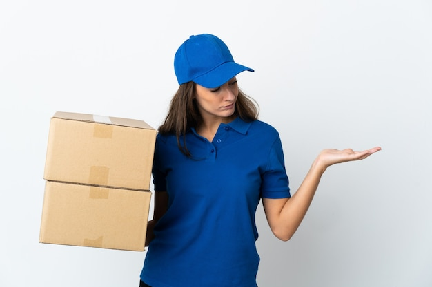 Jeune femme de livraison sur fond blanc isolé holding copyspace avec des doutes