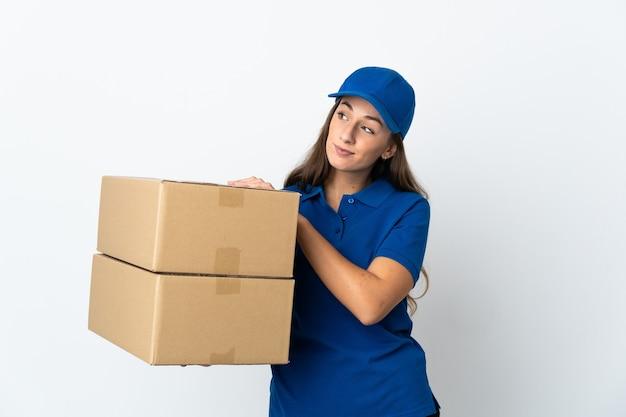 Jeune femme de livraison sur fond blanc isolé en levant tout en souriant