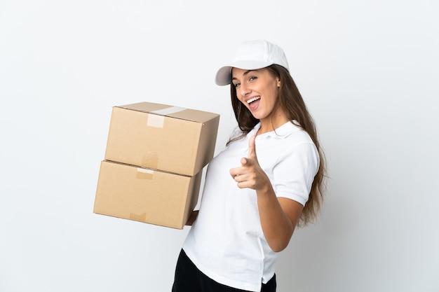 Jeune femme de livraison sur fond blanc isolé pointant vers l'avant et souriant