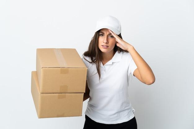 Jeune femme de livraison sur fond blanc isolé regardant loin avec la main pour regarder quelque chose