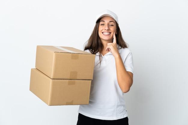 Jeune femme de livraison sur fond blanc isolé souriant avec une expression heureuse et agréable