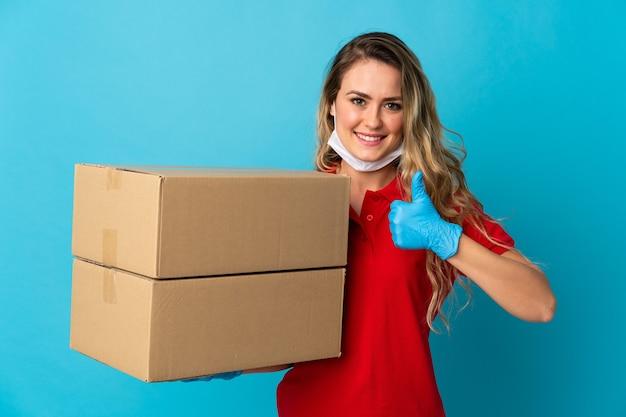 Jeune femme de livraison isolée sur blanc avec les pouces vers le haut parce que quelque chose de bien s'est passé