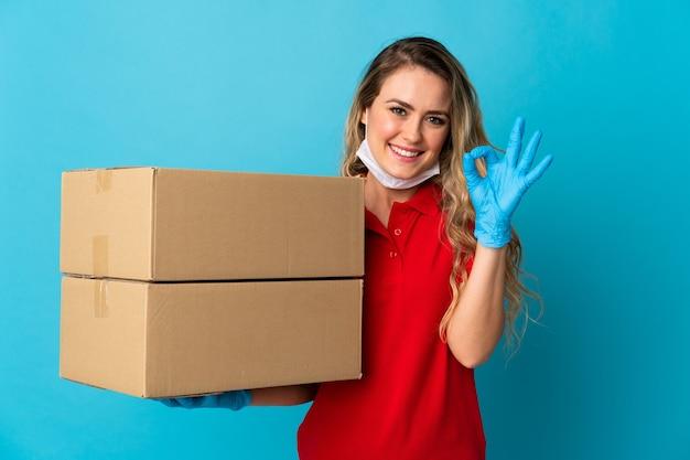 Jeune femme de livraison isolée sur un mur blanc montrant signe ok avec les doigts