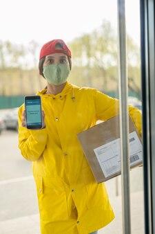 Jeune femme de livraison en masque en tissu et manteau jaune debout avec boîte derrière la porte vitrée et montrant la notification de paiement au client