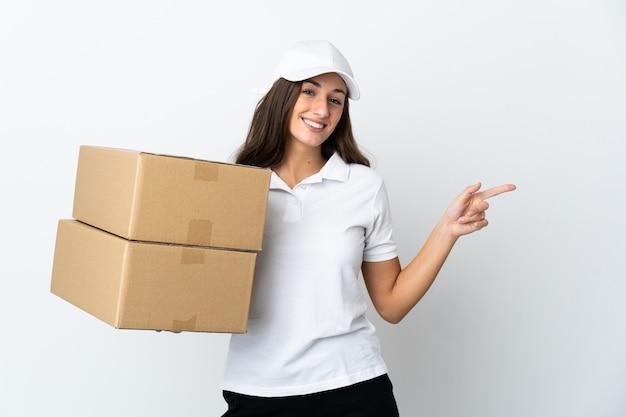 Jeune femme de livraison sur mur blanc isolé doigt pointé sur le côté