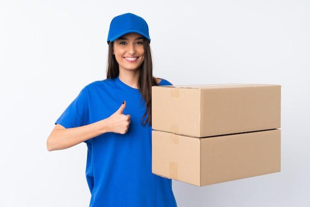 Jeune femme de livraison sur mur blanc isolé donnant un coup de pouce geste