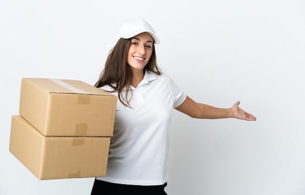 Jeune femme de livraison sur un mur blanc isolé étendant les mains sur le côté pour inviter à venir