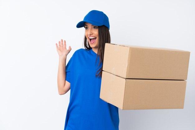 Jeune femme de livraison sur un mur blanc isolé avec une expression faciale surprise