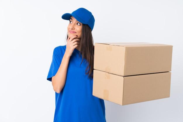 Jeune femme de livraison sur mur blanc isolé en pensant à une idée
