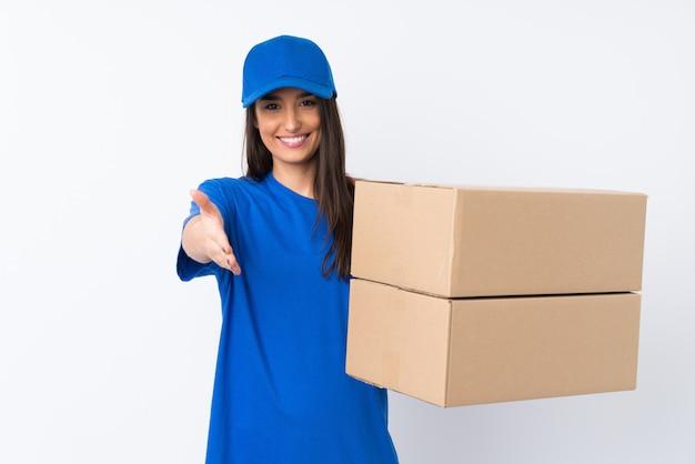 Jeune femme de livraison sur le mur blanc isolé poignée de main après une bonne affaire
