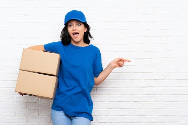 Jeune femme de livraison sur mur de briques blanches surpris et pointant le doigt sur le côté