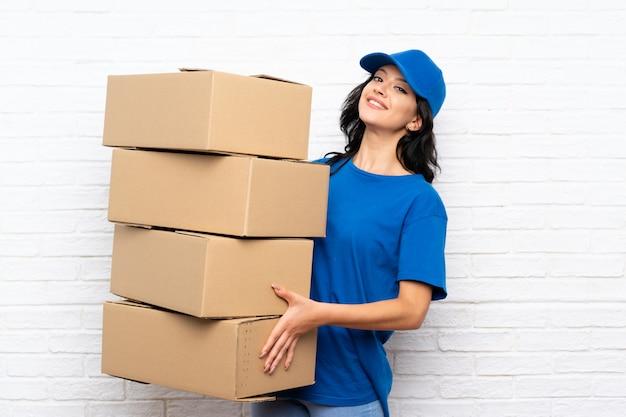Jeune femme de livraison sur mur de briques blanches