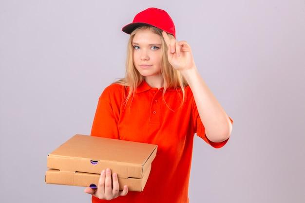 Jeune femme de livraison en polo orange et bonnet rouge pointant sa casquette avec la pensée du doigt axée sur une tâche sur fond blanc isolé