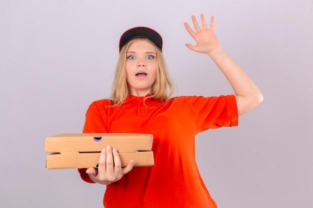 Jeune femme de livraison en polo orange et bonnet rouge à la surprise de garder la bouche ouverte sur fond blanc isolé
