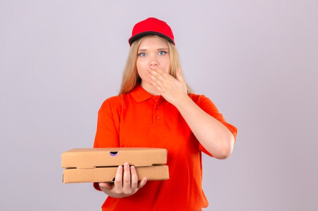 Jeune femme de livraison en polo orange et bonnet rouge tenant des boîtes de pizza à la surprise couvrant la bouche avec la main sur fond blanc isolé