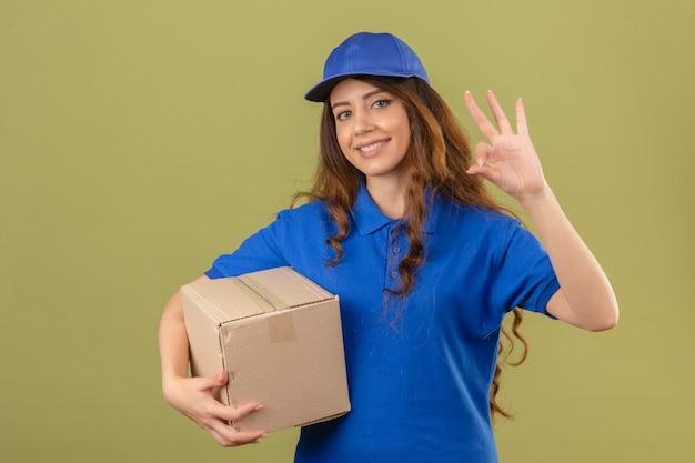 Jeune femme de livraison portant un polo bleu et une casquette debout avec une boîte en carton faisant signe ok smiling friendly sur fond vert isolé