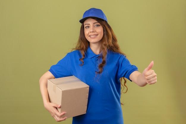 Jeune femme de livraison portant un polo bleu et une casquette debout avec une boîte en carton montrant le pouce vers le haut souriant sur fond vert isolé