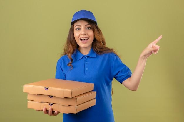 Jeune femme de livraison portant un polo bleu et une casquette debout avec des boîtes de pizza à la surprise souriant pointant avec le doigt sur le côté sur fond vert isolé
