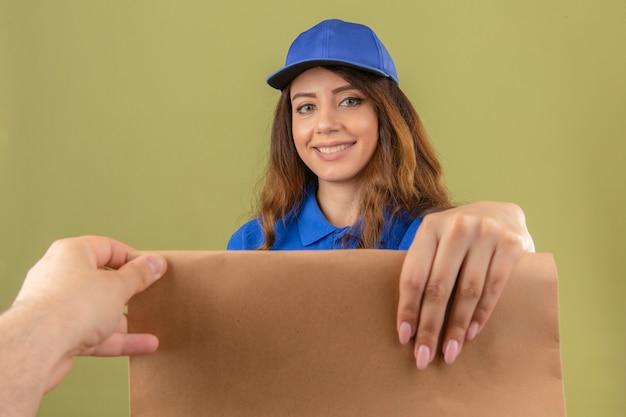 Jeune femme de livraison portant un polo bleu et une casquette donnant un paquet de papier au client souriant sympathique sur fond vert isolé