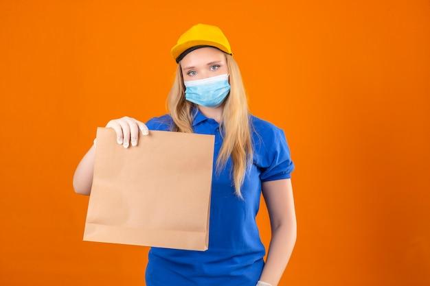 Jeune femme de livraison portant un polo bleu et une casquette jaune en masque de protection médicale montrant un paquet de papier dans les mains à la confiance sur fond jaune foncé isolé