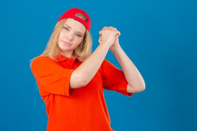 Jeune femme de livraison portant un polo orange et une casquette rouge faisant des gestes avec joint à l'air confiant et fier sur fond bleu isolé